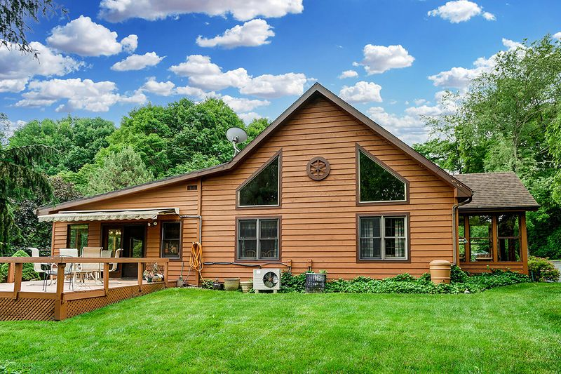 The rear of the property can be seen from most rooms in the home and features a brick patio between the home and detached garage. A large deck includes an electric awning. The family room addition has a wall of windows overlooking the back of the property. CONTRIBUTED PHOTO